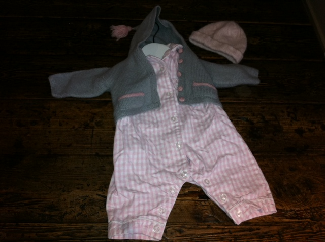 Pink and white check sleepsuit from The White Company, pink cashmere hat from Marie Chantal and grey and pink hooded merino and cashmere cardigan from Sue Hill.